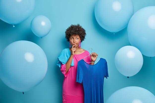Unentschlossene nachdenkliche afroamerikanerin wählt outfit für bankett, überlegt, was sie anziehen soll, hält kleid auf kleiderbügeln, isoliert über blauer wand mit großen luftballons. frauen, mode, kleidung