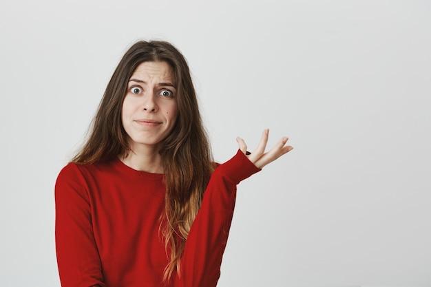 Unentschlossene, unruhige frau kann sich nicht entscheiden, zuckt die achseln und grinst verwirrt