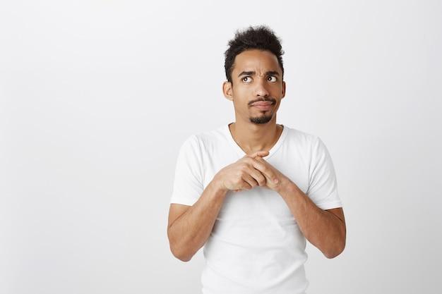 Unentschlossener afroamerikanischer nachdenklicher kerl, der obere linke ecke mit unsicherem ausdruck schaut