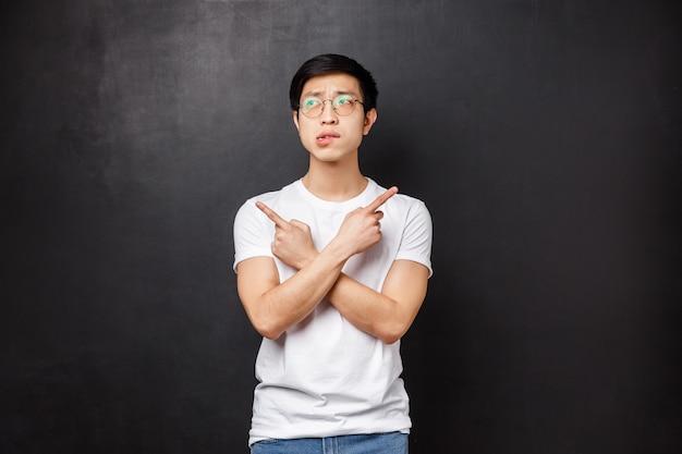 Unentschlossener dummer asiatischer typ weiß nicht, was er wählen soll, zeigt mit den fingern seitlich nach links und rechts auf zwei varianten oder produkte, beißt sich auf die lippen und schaut zögernd weg, als würde er nachdenken und eine entscheidung treffen