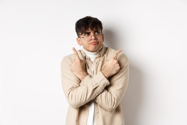 Unentschlossener lustiger junger mann, der probleme mit der wahl hat, mit den fingern seitwärts zeigt und die stirn runzelt, sich zwischen zwei varianten entscheidet und auf weißem hintergrund steht.