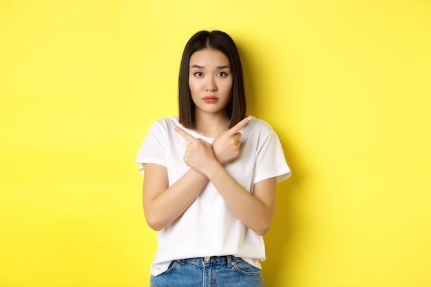 Unentschlossenes asiatisches mädchen braucht hilfe bei der auswahl, zeigt mit den fingern zur seite und sieht verwirrt aus, steht über gelbem hintergrund.