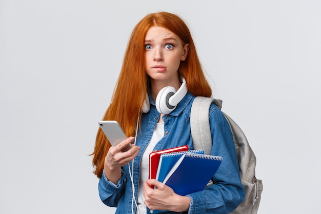 Unentschlossenes, nervöses nettes rothaarige-neulingmädchen, beginnen college des neuen jahres und schauen besorgte kamera, beißen nervös die lippe und halten rucksack, notizbücher und smartphone und lesen mitteilung
