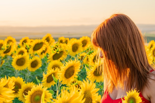 Unerkannte frau, die ein rotes kleid trägt, genießt den tag in einem sonnenblumenfeld.