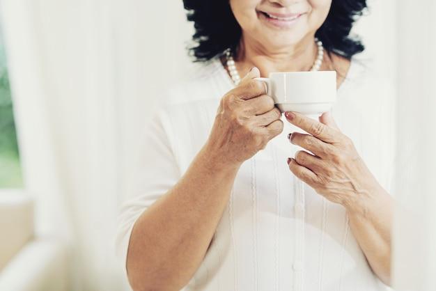 Unerkennbare ältere dame, die zu hause teetasse hält