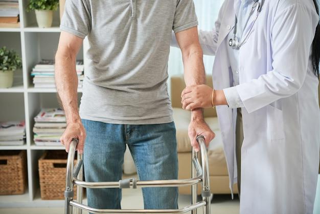 Unerkennbare ärztin, die männlichem patienten hilft, mit gehendem rahmen zu gehen