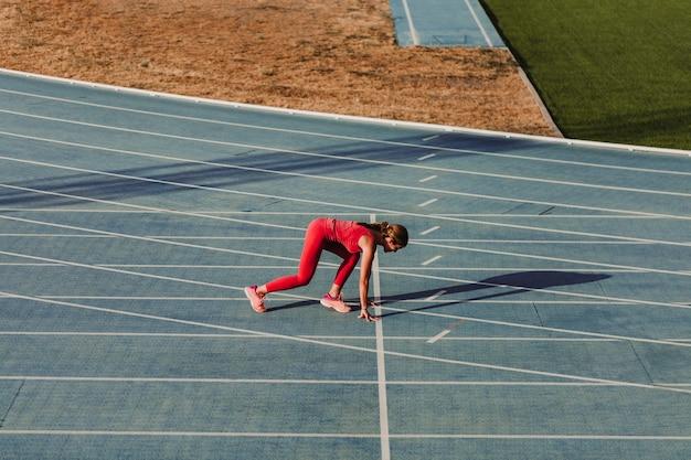 Unerkennbare eignungsfrau auf dem stadion, das durch blaue bahnen läuft
