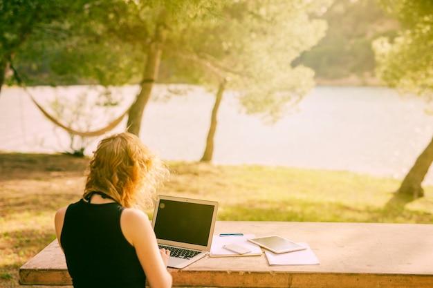 Unerkennbare frau, die am schreibtisch sitzt und an laptop in der natur arbeitet