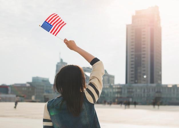 Unerkennbare frau, die amerikanische flagge am unabhängigkeitstag wellenartig bewegt