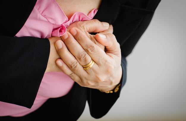 Unerkennbare frau, die an einem plötzlichen herzinfarkt leidet und die brust festhält. konzept der notfallversorgung und betroffen von stauungsversagen oder herz-lungen-wiederbelebung, herzproblemen.