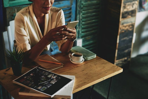 Unerkennbare frau, die bei tisch im café sitzt, kaffee trinkt und smartphone verwendet