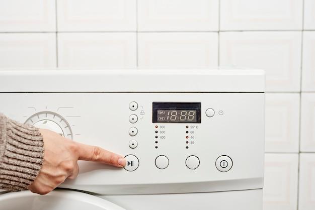 Unerkennbare frau, die einen knopf einer waschmaschine drückt