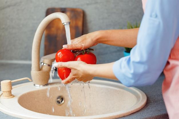 Unerkennbare frau, die frische tomaten im waschbecken wäscht