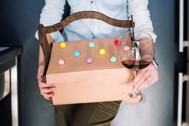 Unerkennbare frau, die geschenke im hölzernen korb und im glas rotwein auf dunklem hintergrund hält. geschenkbox, geschenk, feierkonzept.