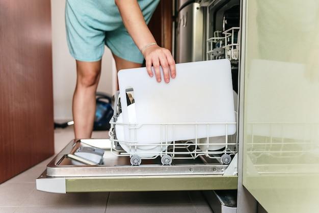 Unerkennbare frau, die geschirr in die spülmaschine stellt