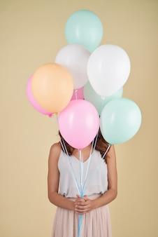 Unerkennbare frau, die im studio mit ihrem gesicht bedeckt mit ballonen aufwirft