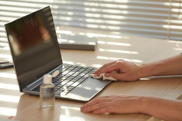 Unerkennbare frau, die laptop während der arbeit am schreibtisch desinfiziert, der durch sonnenlicht beleuchtet wird