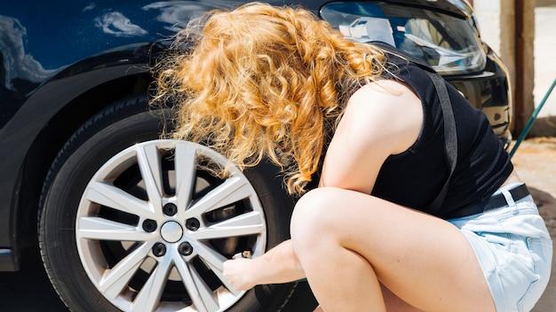 Unerkennbare frau, die reifen des autos an der tankstelle aufpumpt