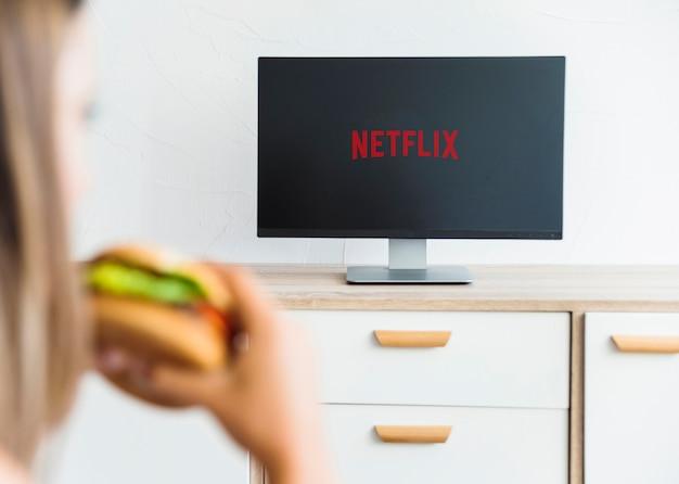 Unerkennbare frau, die reihe im wohnzimmer isst und aufpasst