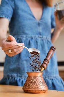 Unerkennbare frau, die türkischen kaffee macht, groung-kaffee in cazve gießt (fokus auf vordergrund)