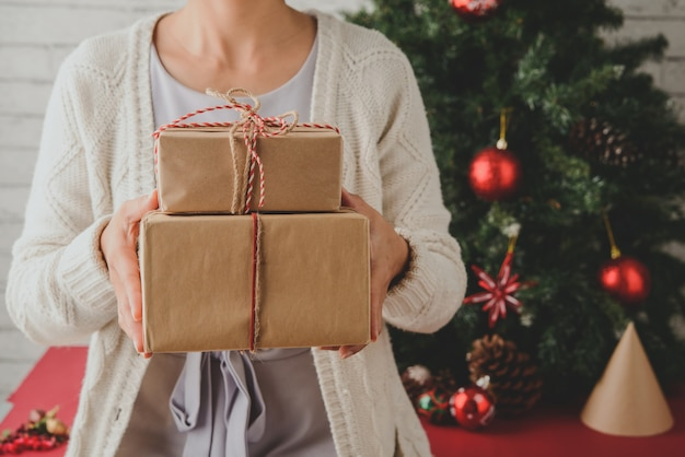 Unerkennbare frau, die zu hause eingewickelte geschenke vor weihnachtsbaum hält