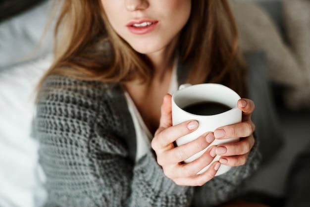 Unerkennbare frau mit kaffeetasse auf dem bett