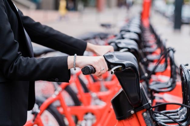Unerkennbare geschäftsfrau, die auf der straße der stadt auf dem weg zur arbeit ein gemeinsames elektrofahrrad mietet?