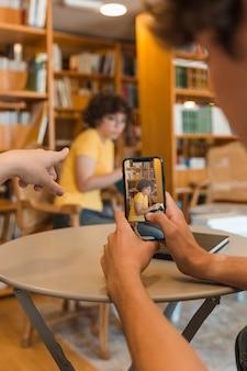 Unerkennbare jugendliche, die foto des studierens von klassenkameraden machen