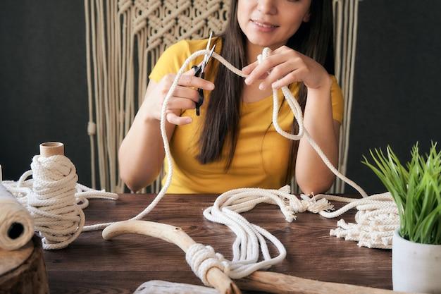 Unerkennbare junge frau, die einen makrameefaden schneidet, um eine dekoration zu machen