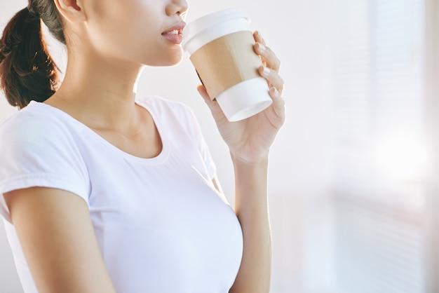 Unerkennbare junge frau, die mitnehmerkaffee am morgen trinkt