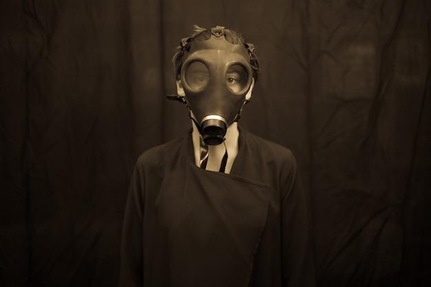 Unerkennbare junge frau in der furchtsamen gasmaske, die kamera bei der stellung betrachtet