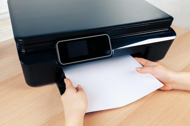 Unerkennbare junge geschäftsfrau, die kopien auf dem fotokopiergerät im büro macht