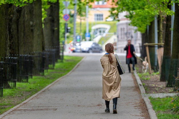 Unerkennbare menschen gehen den bürgersteig durch eine baumallee in einem stadtpark entlang, rückansicht