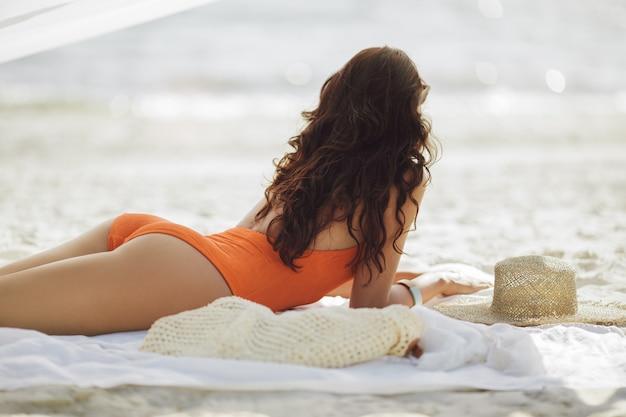 Unerkennbare schöne junge frau im bikini, die am strand von hinten liegt und sonnen