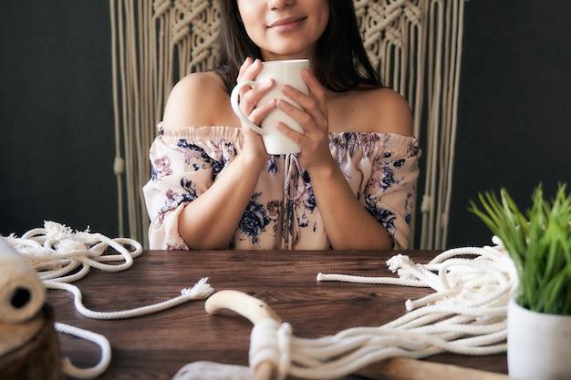 Unerkennbare und glückliche frau, die eine kaffeetasse in einem makramee-arbeitsbereich hält