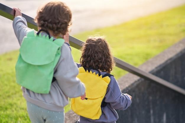 Unerkennbare vorschulkinder klettern mit rucksäcken eine treppe hinunter, die sich am geländer festklammert