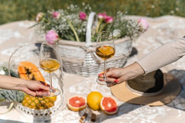 Unerkennbare weibchen, die die arme ausstrecken, um zwei gläser mit weißwein zu zeigen. blankes picknick im hintergrund mit tropischen früchten und blumen.