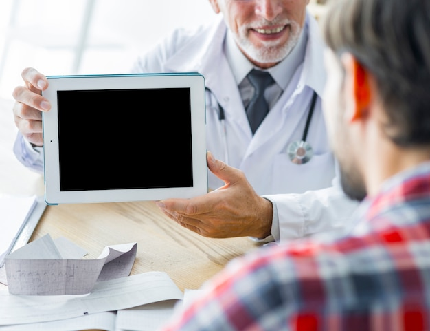 Unerkennbarer doktor, der dem patienten tablette demonstriert