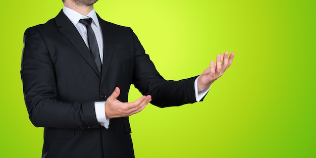 Unerkennbarer geschäftsmann in einem formalen schwarzen anzug, der, kopienraum zeigend sich darstellt