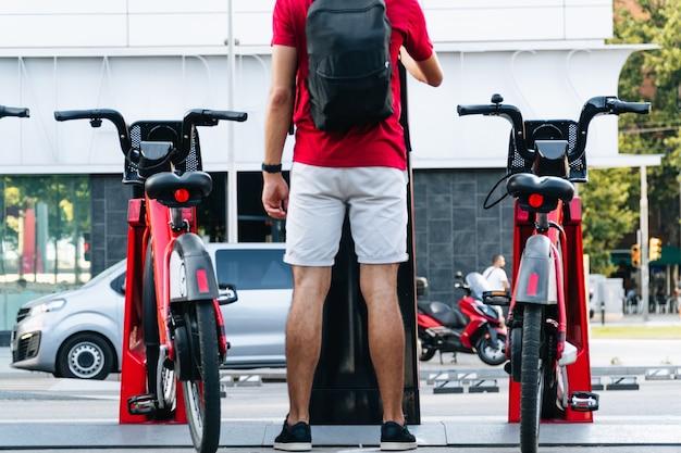 Unerkennbarer junger erwachsener student, der in einer großstadt ein fahrrad mietet