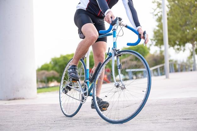 Unerkennbarer junger männlicher radfahrer in der sportkleidung, die fahrrad auf straße im park radfährt