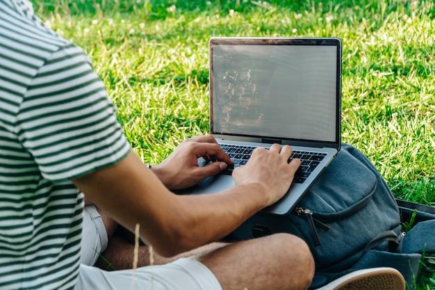 Unerkennbarer junger weißer digitaler nomade, der aus der ferne an einem laptop arbeitet