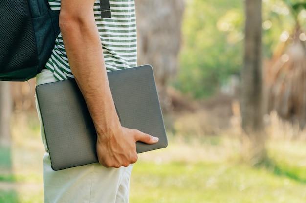 Unerkennbarer junger weißer mann, der einen laptop mit einem park im hintergrund hält