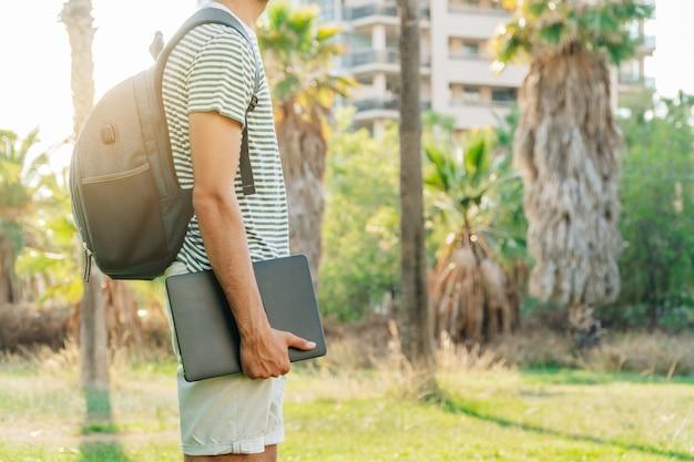 Unerkennbarer junger weißer mann mit rucksack, der einen laptop mit einem park im hintergrund hält
