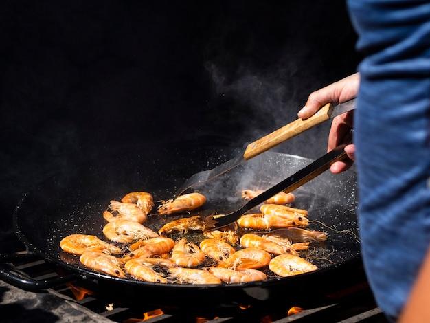 Unerkennbarer koch, der die garnelen braten auf großer wanne leicht schlägt
