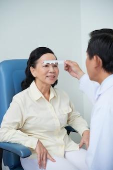 Unerkennbarer männlicher augenarzt, der sehkraftprüfung für asiatischen weiblichen patienten durchführt