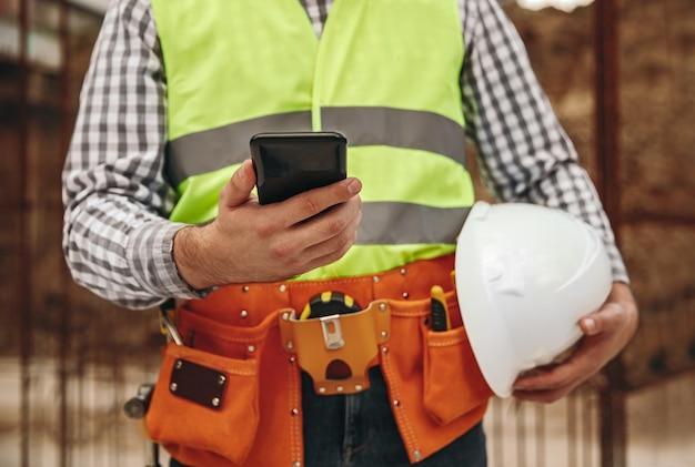 Unerkennbarer männlicher baumeister mit helm-browsing-app auf dem smartphone während der pause auf der baustelle