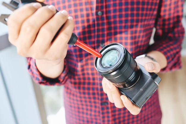 Unerkennbarer männlicher fotograf, der kameraobjektiv mit luftgebläse säubert