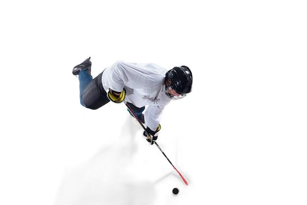 Unerkennbarer männlicher hockeyspieler mit dem stock auf dem eisplatz auf weiß