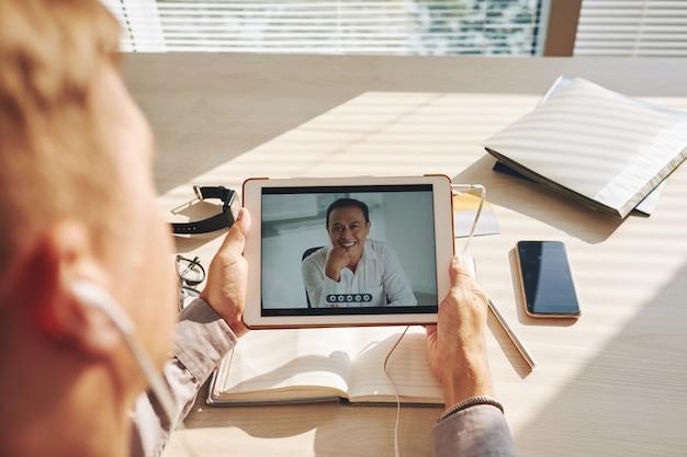 Unerkennbarer mann, der am schreibtisch sitzt und videoanruf auf tablette hat